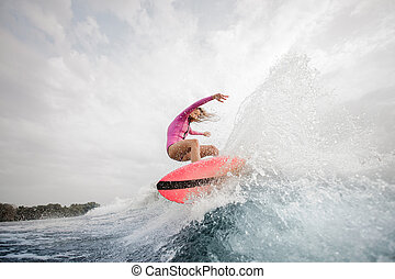 Active girl jumping on the orange wakeboard