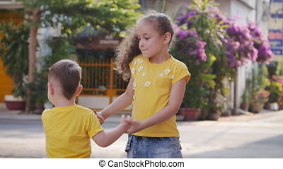 Active girl or sister nanny and cute little baby boy jumping dancing on the street holding hands, happy family daughter and son, children enjoy playing fun action game together.
