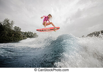 Active girl riding on the orange wakeboard
