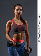 Active girl with perfect body shape keeping black dumbbells