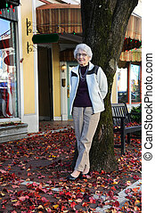 Active Grandmother Shopping - Active senior rests, against a...