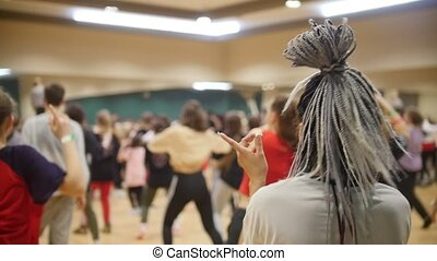 Active group dances. A woman with grey african braids. Slow...
