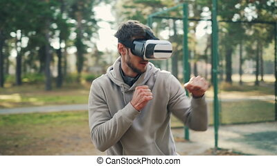 Active guy is wearing augmented reality glasses and boxing...