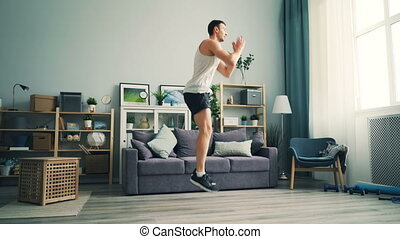Active guy jumping at home doing sports on floor of flat practising working out