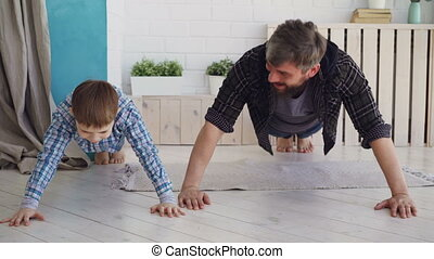 Active handsome father and his joyful son are exercising...