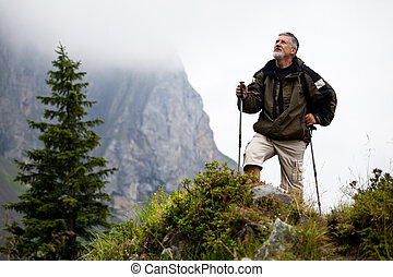 active handsome senior man nordic walking outdoors on a...