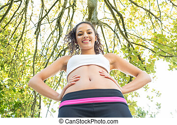 Active happy brunette standing hands on hips smiling in a ...