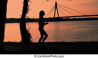 silhouette woman running near river. beautiful landscape bridge over river. runner wearing sportswear hoodie and sneakers