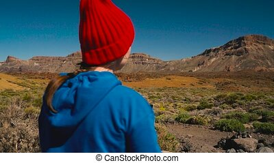 Active hiker woman hiking on Teide National Park and makes...