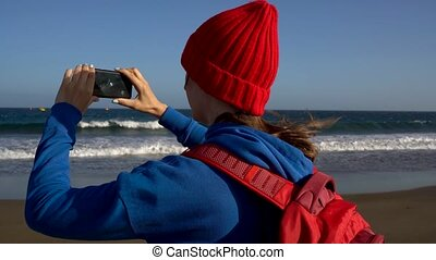 Active hiker woman walks on the beach and makes photo on her smartphone. Caucasian young woman with backpack on Tenerife, Canary Islands, Spain