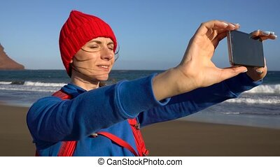 Active hiker woman walks on the beach and makes self photo on her smartphone. Caucasian young woman with backpack on Tenerife, Canary Islands, Spain