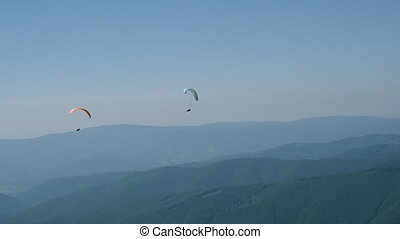 Active hobby paragliding in sunny day. - two paraglides...