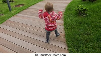 Active kid in red sweater walking on wooden path - Back view...