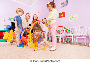 Active kindergarten class kids crawl though hoops - Little...