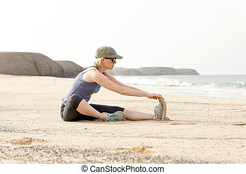 Active Lady Doing Seated Hamstring Stretch by the Beach