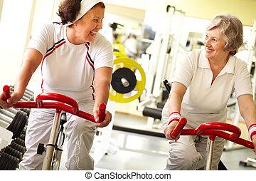 Active lifestyle - Two senior women training on simulator ...