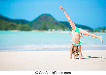 Active little girl at beach having a lot of fun. Cute kid making sporty exercises on the seashore