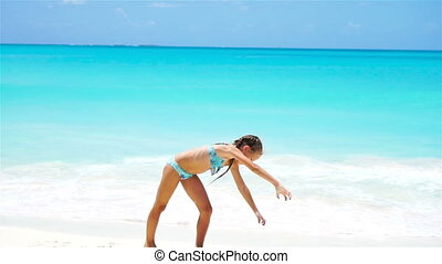 Active little girl at beach having a lot of fun. Sporty kid makes the wheel on the seashore