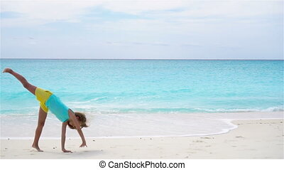 Active little girl at beach having a lot of fun. Sporty kid makes the wheel on the seashore in slow motion