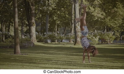 Active little girl doing cartwheel on green grass - Healthy...