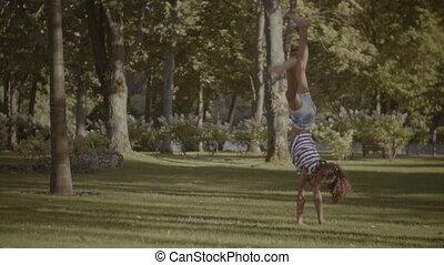 Active little girl doing cartwheel on green grass - Healthy...