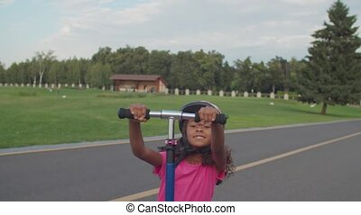 Active smiling cute preadolescent african girl with curly hair in protective helmet making trick while riding on push scooter in park, enjoying leisure and freedom, expressing positivity and happiness