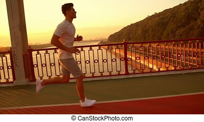 active male runner doing cardio - jogger training on the...