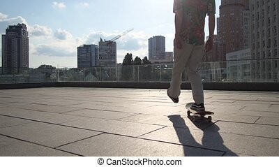Active male skater picking up board during riding - Back...