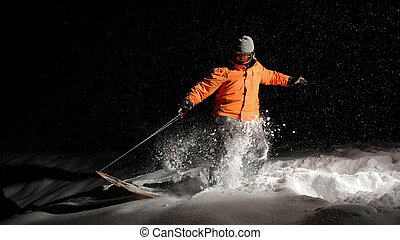 Active male snowboarder in orange sportswear and mask jumping on a snowy hill at night