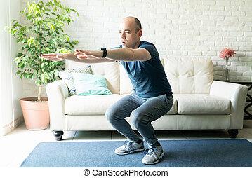 Active man doing squats at home
