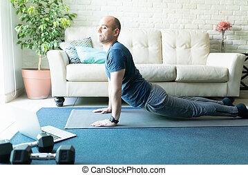 Active man doing yoga at home