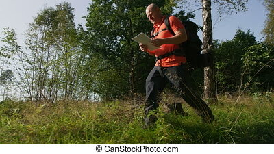 Active man hiker navigate using map and compass in beautiful...