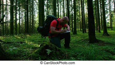Active man hiker navigates using map and compass in...