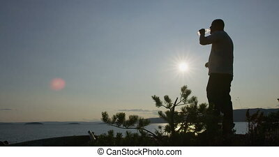 Active man hiker takes a break and drinking water by the sea...