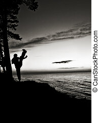 Active man training martial arts near the beach. Kicking...