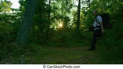 Active man with backpack hiking on path in beautiful forest at sunset