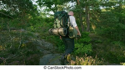 Active man with backpack walking on mountain path at sunset...