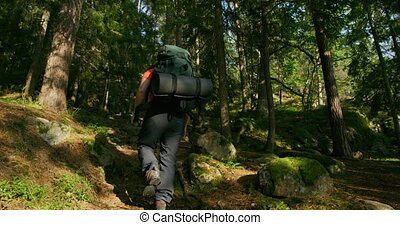 Active man with large backpack hiking in steep mountain path...