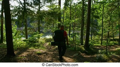 Active man with large backpack walks down steep mountain...