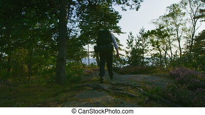 Active man with large backpack walks on the mountain by the sea at sunset