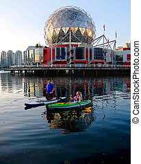 Active married couple boating and kayaking in city harbor False Creek near Yaletown.