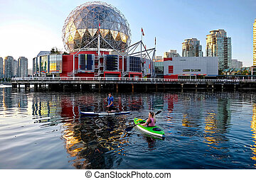 Active married couple paddling and kayaking in English Bay near Science World  in summer.