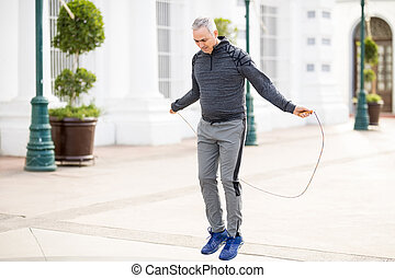 Active mature man exercising with jump rope