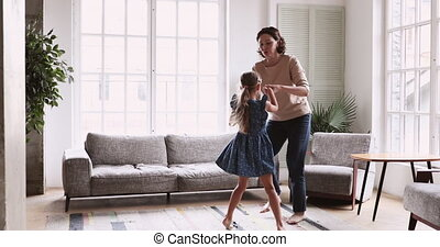 Active middle aged granny dancing barefoot with granddaughter.