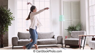 Active mom and child daughter jumping dancing in living room