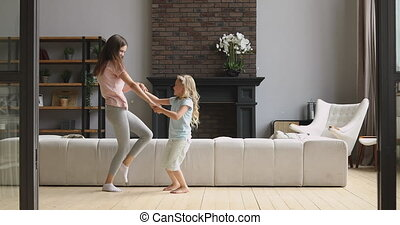 Active mom and kid daughter dancing together in living room