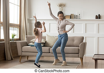 Active mother dancing at home with little daughter