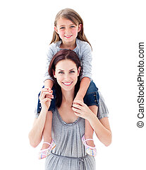 Active mother giving her daughter piggyback ride against a...