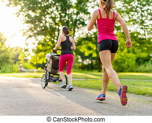 active mother jogging - Woman pushing her little girl in a ...