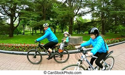 Active Mother With Children Cycling In Green Park